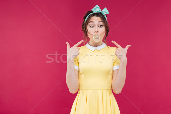 Wondered pinup girl pointing on pink bubble of chewing gum Stock photo © deandrobot