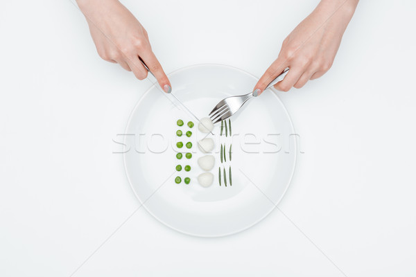 Hands of young woman eating green peas, mozzarella and herbs Stock photo © deandrobot