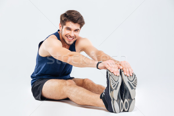 Happy handsome young man athlete sitting and stretching Stock photo © deandrobot