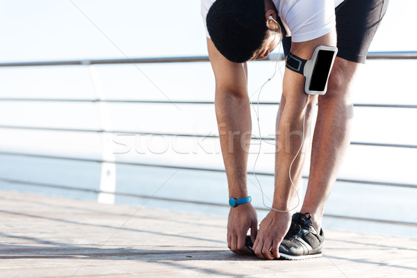 Sportsman stretching and listening to music from blank screen smartphone Stock photo © deandrobot
