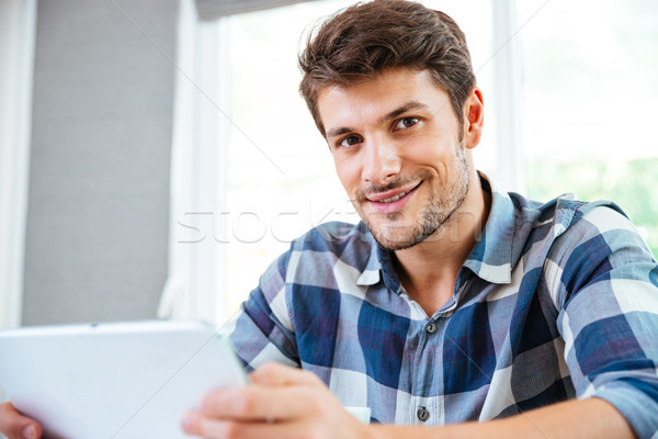 Happy young man in checkered shirt using tablet at home Stock photo © deandrobot
