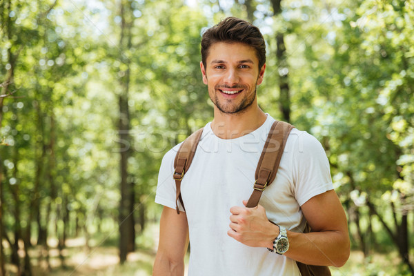 Closeup of cheerful young man standing and smiling in forest Stock photo © deandrobot