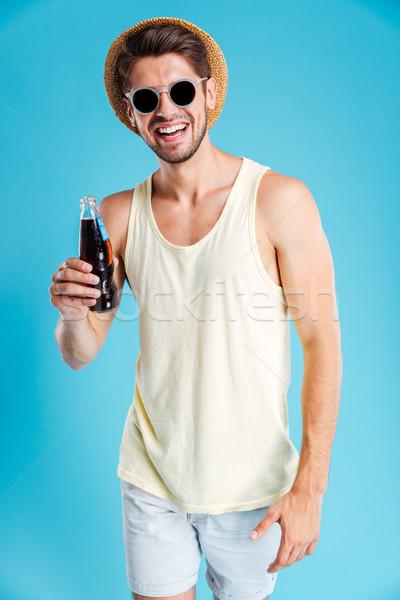Jeune homme chapeau lunettes de soleil potable soude Photo stock © deandrobot