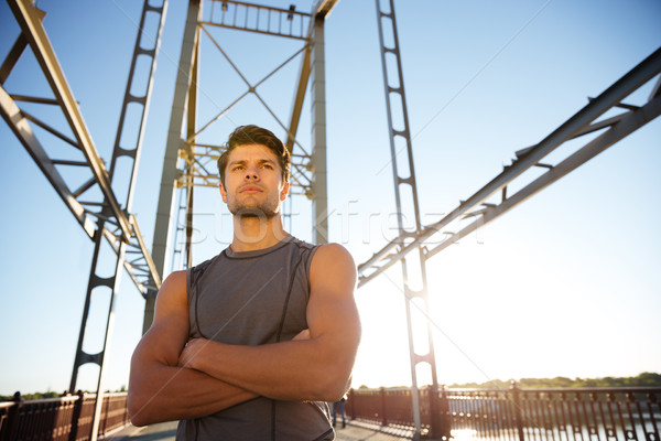 Sports man resting after running with hands crossed on bridge Stock photo © deandrobot