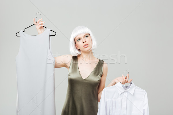 Confused beautiful young woman choosing between shirt and dress Stock photo © deandrobot