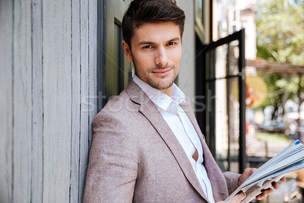 Close-up portrait of a man standing with newspaper outdoors Stock photo © deandrobot