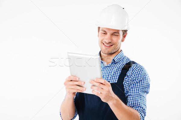 Szczęśliwy uśmiechnięty mężczyzna budowniczy pc tabletka Zdjęcia stock © deandrobot