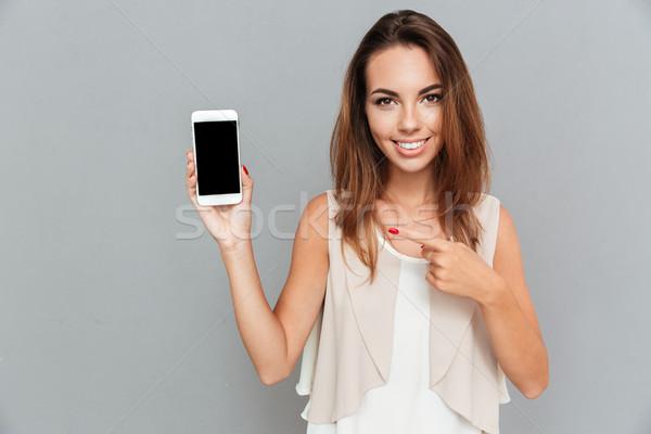 Mosolyog fiatal nő mutat ujj okostelefon képernyő Stock fotó © deandrobot