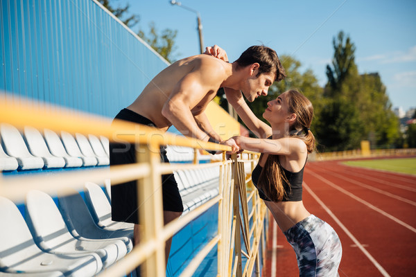 Sports couple in love hugging on athletics track field Stock photo © deandrobot
