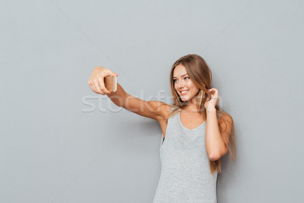 Smiling young girl making selfie photo isolated Stock photo © deandrobot