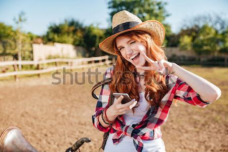 Redhead cowgirl using mobile phone while standing at ranch fence Stock photo © deandrobot