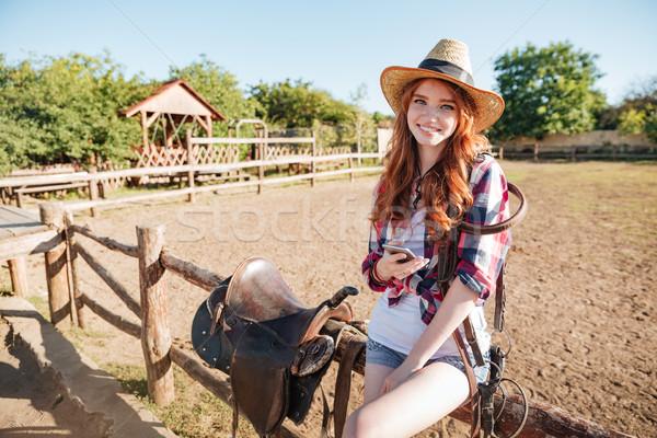улыбающаяся женщина Постоянный мобильного телефона ранчо улыбаясь довольно Сток-фото © deandrobot