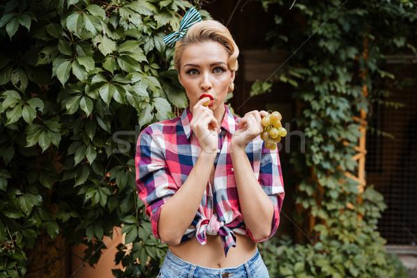 Zdziwiony cute pinup dziewczyna jedzenie winogron Zdjęcia stock © deandrobot