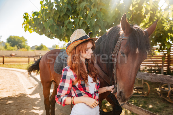 Stock photo: Woman cowgirl standing and taking care of horse in village