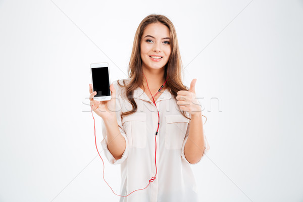 Beautiful young girl listening music with earphones Stock photo © deandrobot