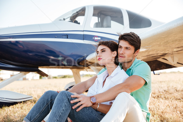 Couple sitting and hugging near small plane Stock photo © deandrobot
