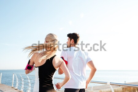 Young couple doing stretching exercise and warming up before jogging Stock photo © deandrobot