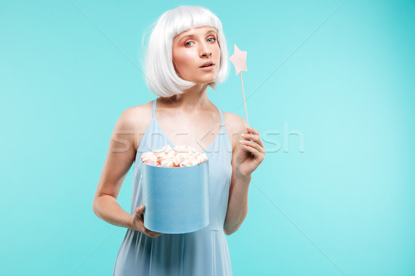 Portrait of attractive young woman with marshmallows and magic wand Stock photo © deandrobot
