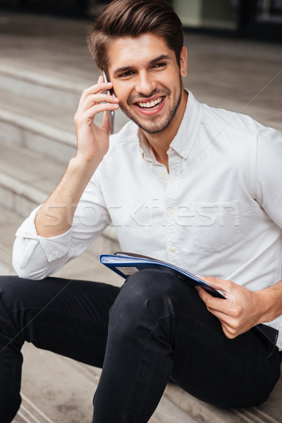 Cheerful young businessman talking on mobile phone outdoors Stock photo © deandrobot