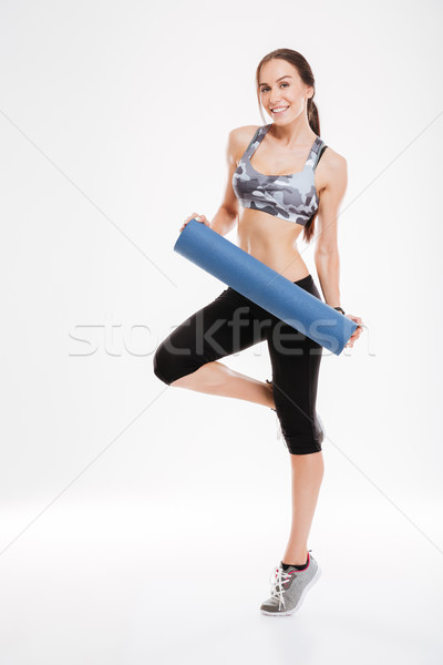 Full length of happy fitness woman with mat Stock photo © deandrobot