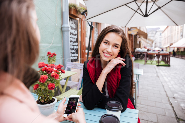Two women talking and using cell phone in outdoor cafe Stock photo © deandrobot