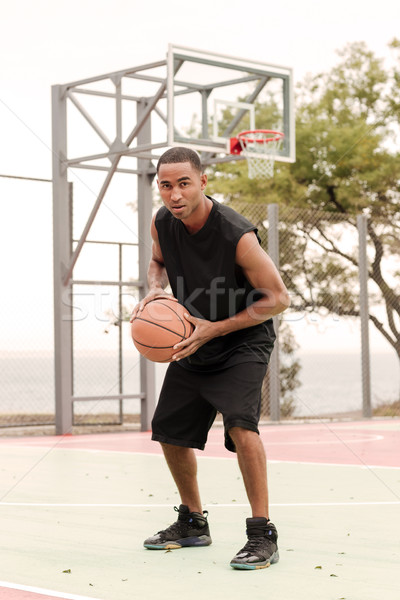 Young attractive african sports man holding basketball outdoors Stock photo © deandrobot