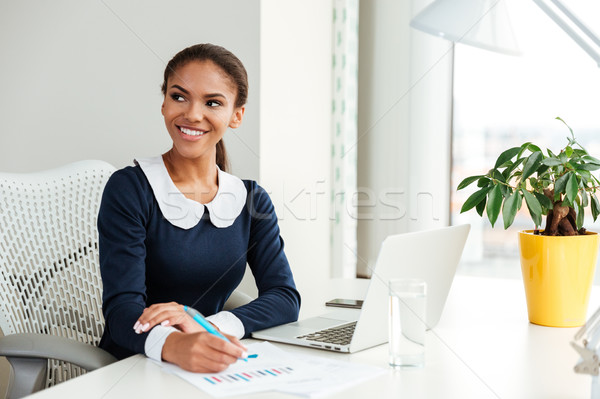 Stock photo: Smiling african business woman writing on workplace