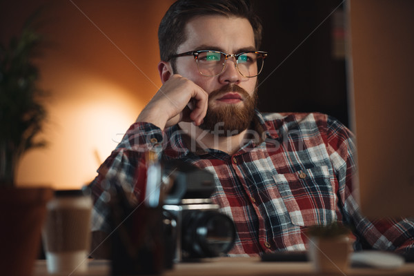 Concentrated bearded web designer working late at night Stock photo © deandrobot
