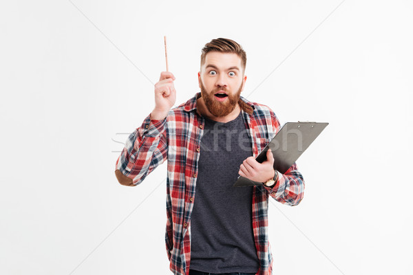 Happy man in plaid shirt holding clipboard and having idea Stock photo © deandrobot