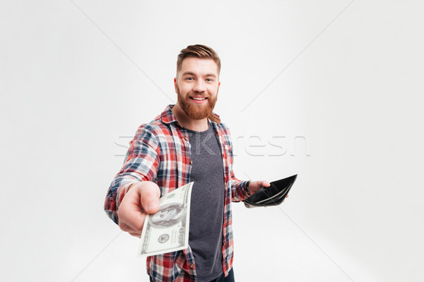 Smiling man in plaid shirt giving money from his wallet Stock photo © deandrobot