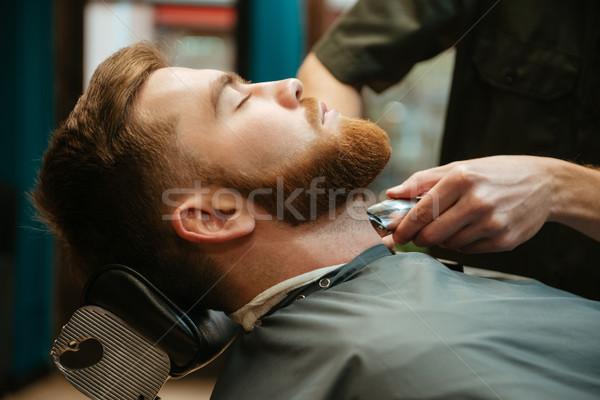 Photo of young man getting beard haircut Stock photo © deandrobot