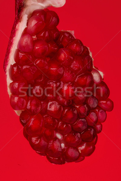 Pomegranate piece on red background Stock photo © deandrobot