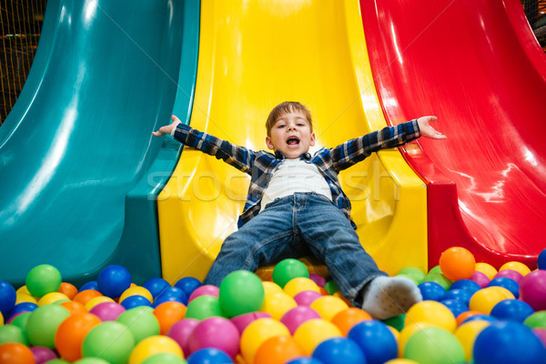 Little boy playing on slide and pool with colorful balls Stock photo © deandrobot