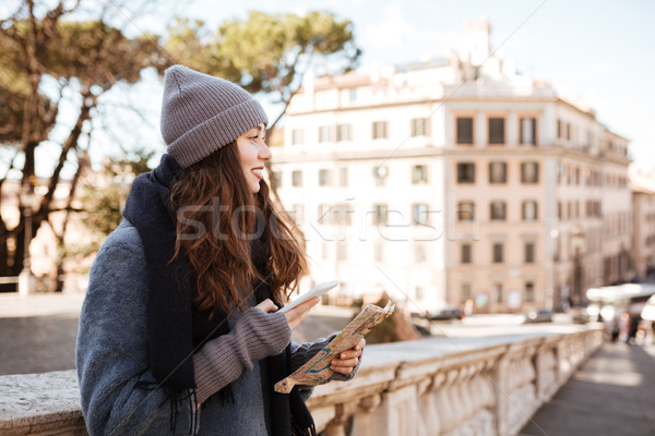 Smiling woman with map and mobile phone standing in city Stock photo © deandrobot