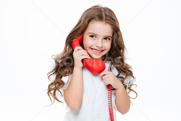 Happy curly little girl standing and talking on red telephone Stock photo © deandrobot