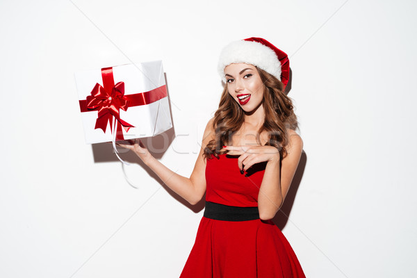 Woman in red santa costume pointing finger at gift box Stock photo © deandrobot
