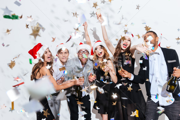 Cheerful excited friends in santa claus hats celebrating new year Stock photo © deandrobot