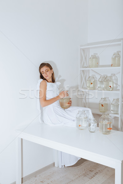 Relaxed tired young woman with gold fish sleeping on table Stock photo © deandrobot