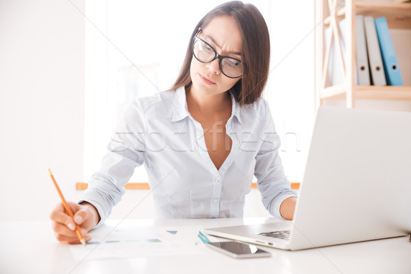 Businesswoman sitting in her office and writing notes Stock photo © deandrobot
