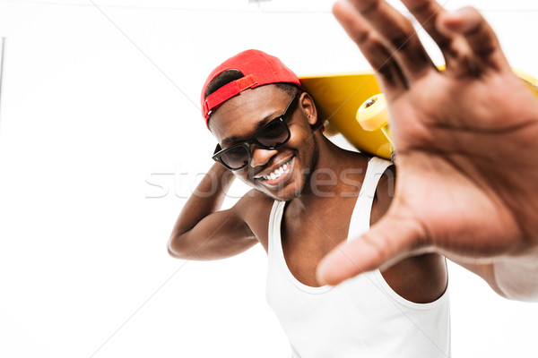 Cheerful african man holding skateboard and stretching hands to camera Stock photo © deandrobot