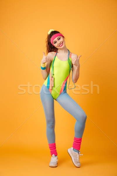 Cheerful sportswoman with jumping rope standing and showing thumbs up Stock photo © deandrobot
