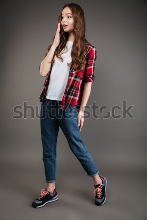 Surprised attractive young woman in plaid shirt and jeans walking Stock photo © deandrobot