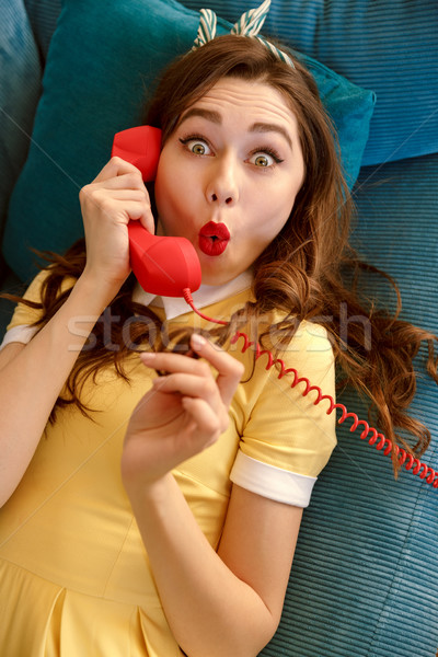 Top view of shocked woman talking at handset Stock photo © deandrobot