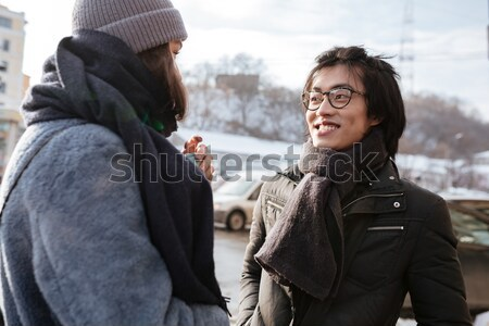 Cheerful young asian man with caucasian lady gives a high-five Stock photo © deandrobot