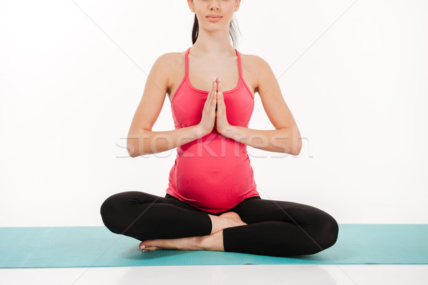 Young pregnant woman sitting in lotus position on the mat Stock photo © deandrobot