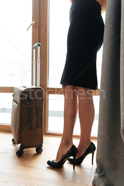 Woman in high heels standing at the window with suitcase Stock photo © deandrobot