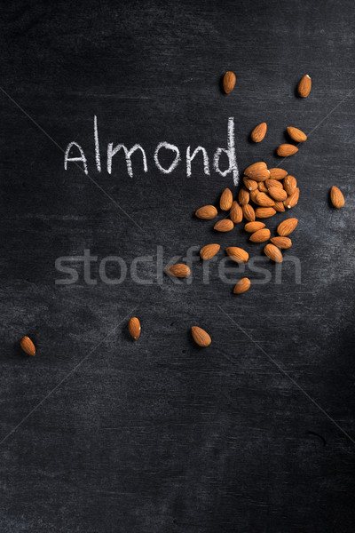 Almond over dark chalkboard background Stock photo © deandrobot
