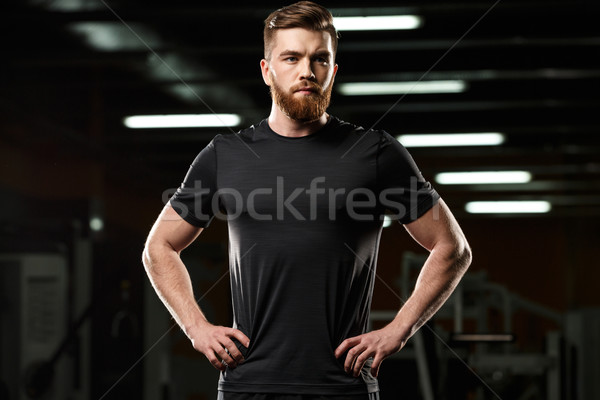 Serious sports man standing and posing in gym Stock photo © deandrobot