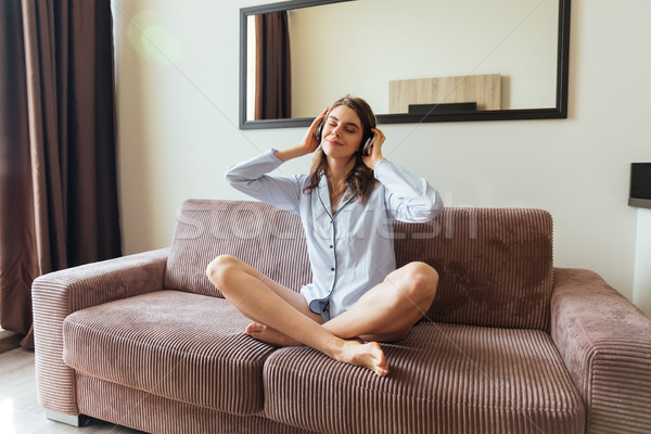 Pretty young lady dressed in pajama listening music. Stock photo © deandrobot