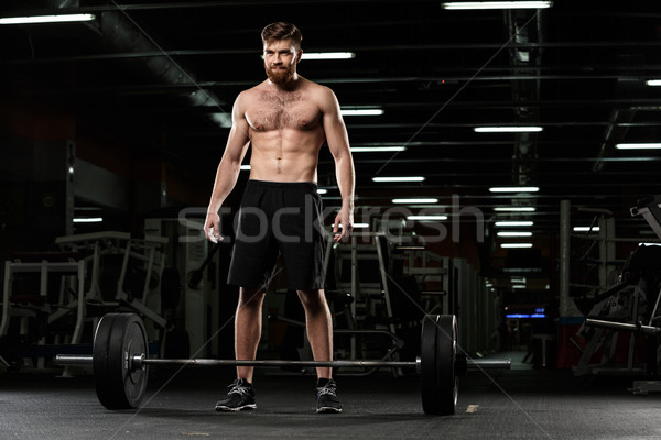 Smiling strong sports man make sport exercises with barbell Stock photo © deandrobot